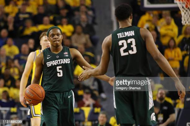 Cassius Winston of the Michigan State Spartans celebrates a second half play with Xavier Tillman while playing the Michigan Wolverines at Crisler...