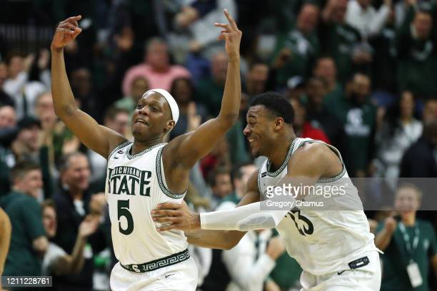 Cassius Winston of the Michigan State Spartans celebrates a second half three pointer with Xavier Tillman Sr #23 while playing the Ohio State...