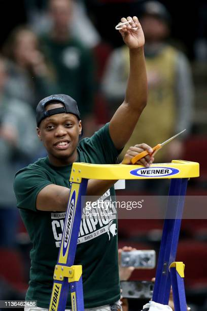 Cassius Winston of the Michigan State Spartans cuts down the net after beating the Michigan Wolverines 6560 in the championship game of the Big Ten...