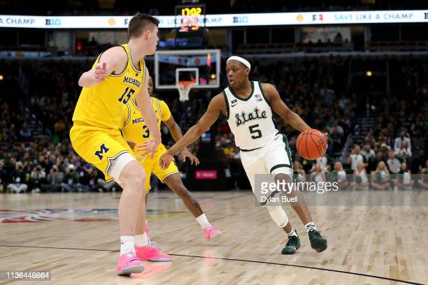 Cassius Winston of the Michigan State Spartans dribbles the ball while being guarded by Jon Teske of the Michigan Wolverines in the first half during...