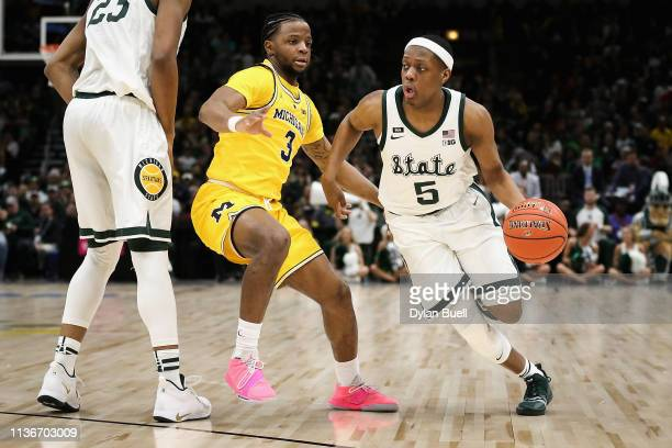 Cassius Winston of the Michigan State Spartans dribbles the ball while being guarded by Zavier Simpson of the Michigan Wolverines in the first half...