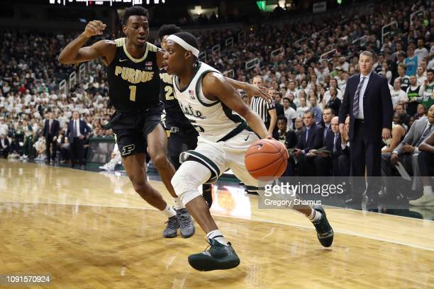 Cassius Winston of the Michigan State Spartans drives around Aaron Wheeler of the Purdue Boilermakers during the first half at Breslin Center on...