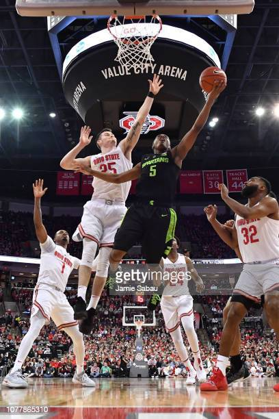 Cassius Winston of the Michigan State Spartans drives past Kyle Young of the Ohio State Buckeyes for a layup in the second half on January 5 2019 at...