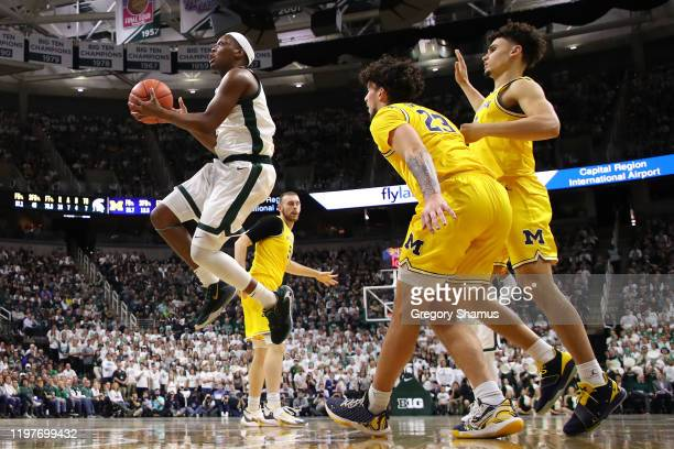 Cassius Winston of the Michigan State Spartans drives the basket past Brandon Johns Jr #23 of the Michigan Wolverines during the first half at...