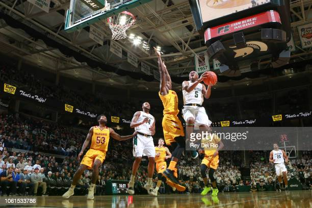 Cassius Winston of the Michigan State Spartans drives to the basket against Travis Munnings of the Louisiana Monroe Warhawks at Breslin Center on...