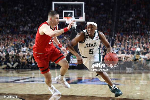 Cassius Winston of the Michigan State Spartans drives to the basket against Matt Mooney of the Texas Tech Red Raiders in the first half during the...
