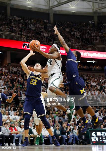 Cassius Winston of the Michigan State Spartans drives to the basket and draws a foul for Zavier Simpson of the Michigan Wolverines at Breslin Center...