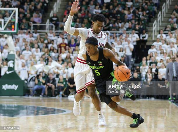 Cassius Winston of the Michigan State Spartans drives to the basket while defended by Devonte Green of the Indiana Hoosiers at Breslin Center on...