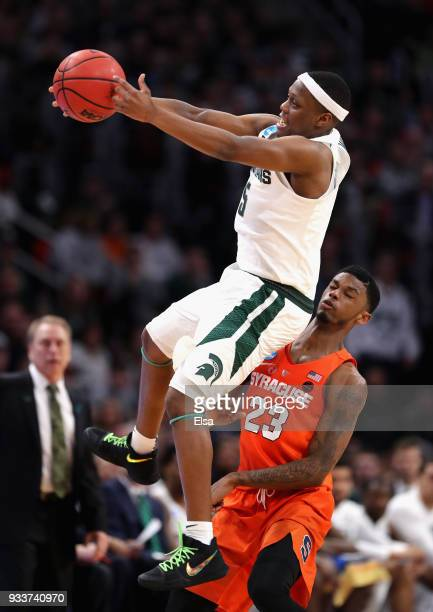 Cassius Winston of the Michigan State Spartans falls as he attempts to catch an inbounds pass against Frank Howard of the Syracuse Orange during the...