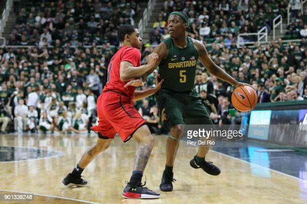 Cassius Winston of the Michigan State Spartans handles the ball defended by Anthony Cowan Jr #1 of the Maryland Terrapins at Breslin Center on...