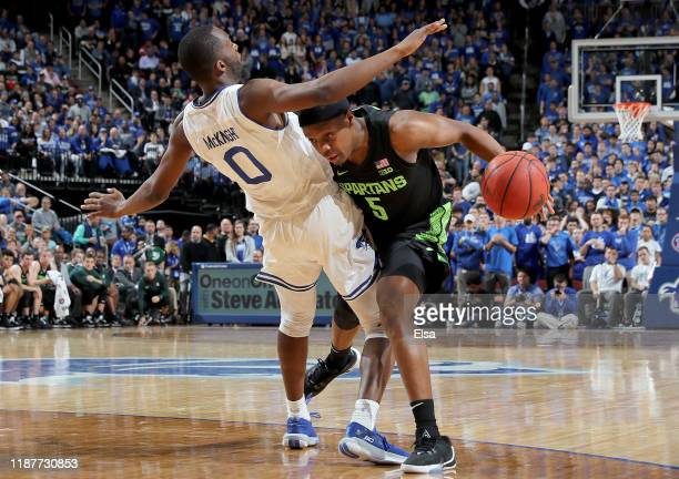 Cassius Winston of the Michigan State Spartans heads for the net as Quincy McKnight of the Seton Hall Pirates defends in the first half at Prudential...
