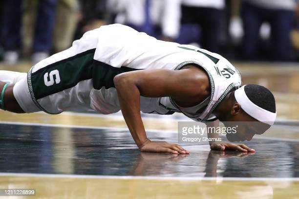 Cassius Winston of the Michigan State Spartans kisses the center court logo at the Breslin Center after leaving the floor in his final home game on...