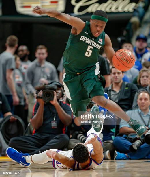 Cassius Winston of the Michigan State Spartans leaps over Devon Dotson of the Kansas Jayhawks during the game at Bankers Life Fieldhouse on November...