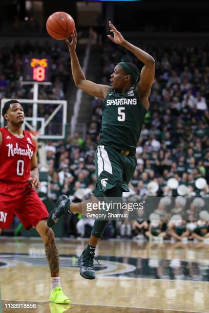 Cassius Winston of the Michigan State Spartans looks to pass in front of James Palmer Jr #0 of the Nebraska Cornhuskers at Breslin Center on March 05...