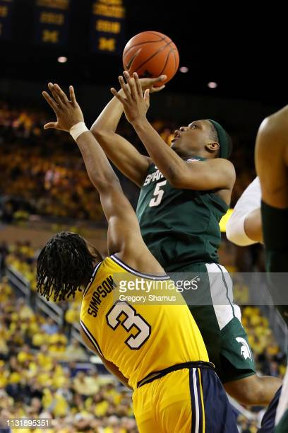Cassius Winston of the Michigan State Spartans takes a shot over Zavier Simpson of the Michigan Wolverines during the second half at Crisler Arena on...