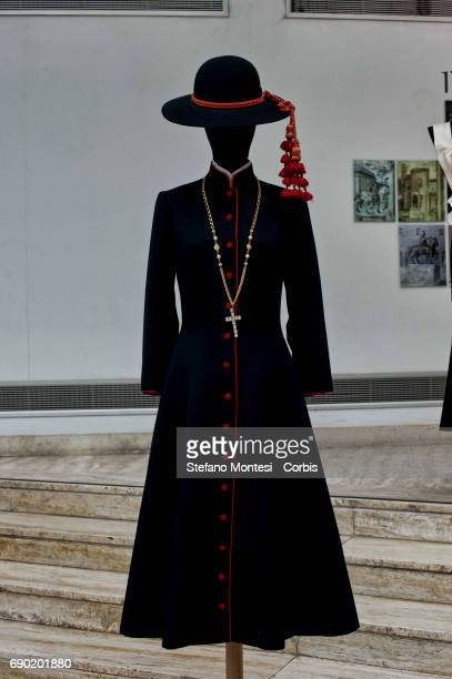 Cassock style coat dress in black woolsilk with red trimming and small buttons A Monsignor hat with cord and tassel a necklacechain with cross...