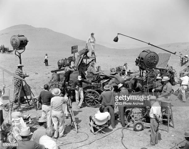 Cast and crew members of the TV western 'Gunsmoke' film an episode in a desert location June 8 1961 Standing on a platform is American actor Dennis...