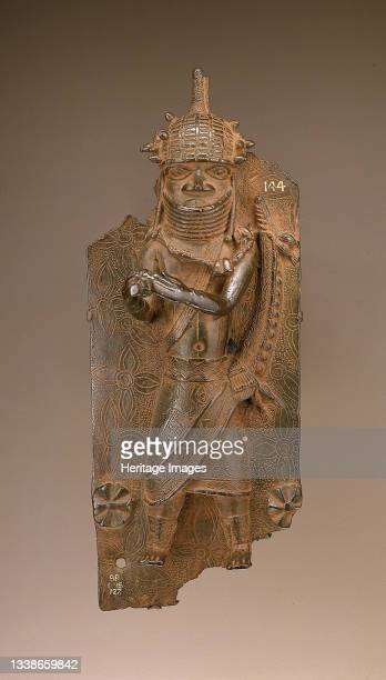 Cast copper alloy plaque showing a man with a rattle, a net covered sphere, in outstretched hands. Incised foliate background with two relief...