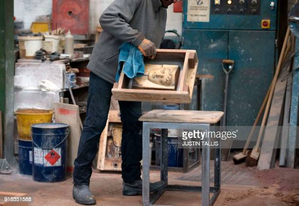 A cast for a BAFTA is lifted onto a work bench during a photo call at the New Pro Foundries west of London on February 7 2018 ahead of the British...