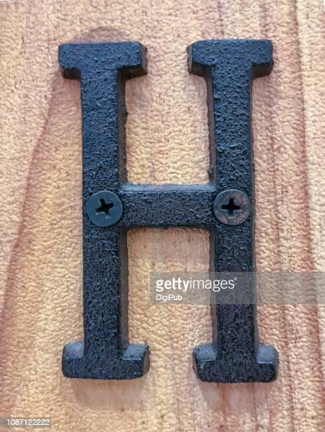 cast iron capital letter h on wood board - letra h - fotografias e filmes do acervo