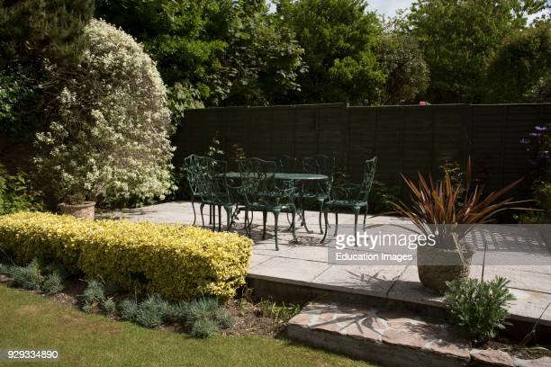 Cast iron garden furniture A table and chairs painted dark green Devon England UK