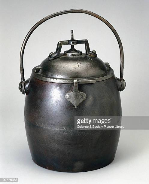 Cast iron pressure cooker of four quart capacity with latches to secure the lid and steam release safety valve in centre of lid made by E Pugh and Co...