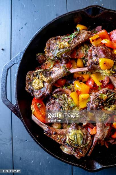 cast iron skillet filled with gourmet lamb chops and a vegetable medley of brussels sprouts, bell pepper, garlic, leeks tomato, garlic and pesto - shank stock pictures, royalty-free photos & images