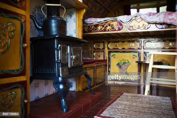 a cast iron stove with large metal kettle, a mantelpiece and storage cupboards and raised bed, the interior of a gypsy caravan, - gypsy caravan stock pictures, royalty-free photos & images