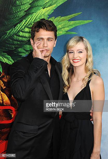 Cast member James Franco gestures as if smoking a marijuana cigarette as he arrives with his girlfriend Ahna O'Reilly for the premiere of the film...