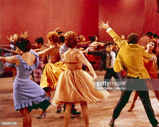 Cast members dance in a gymnasium set in a scene from 'West Side Story' 1961