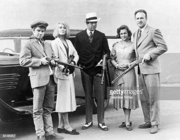 Cast members from director Arthur Penn's film, 'Bonnie & Clyde,' pose with machine guns in front of a car. Left to right: Michael J Pollard, Faye...