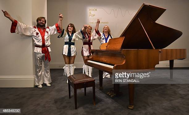 "Cast members from the musical 'Bjorn Again' pose alongside a ""Bolin Grand Piano,"" made by Swedish designer Georg Bolin, during a photocall to promote..."