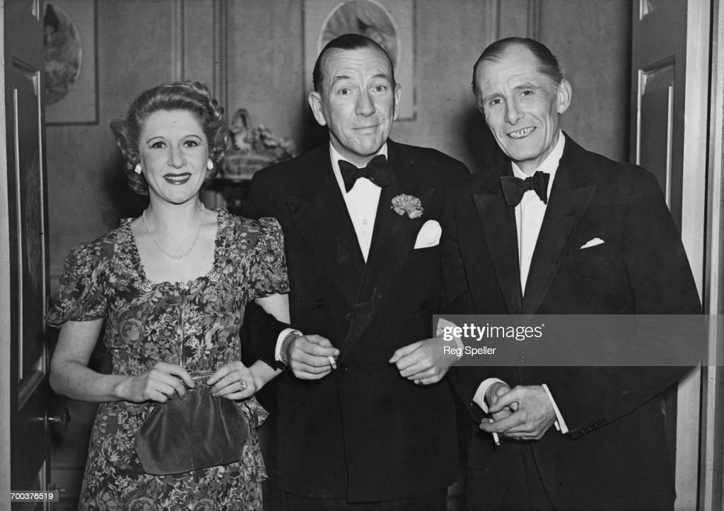 Cast members Moya Nugent (1901 - 1954) and Martin Lewis (1888 - 1970, right) at the Duchess Theatre, London, with director and playwright Noel Coward (1899 - 1973) at the last performance of Coward's play, 'Blithe Spirit', after a record-breaking, five-year run of 1997 performances, 11th March 1946.