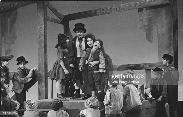 Cast members of the Broadway production 'Oliver!', including British actors David Jones as the Artful Dodger and Georgia Brown , perform on an...
