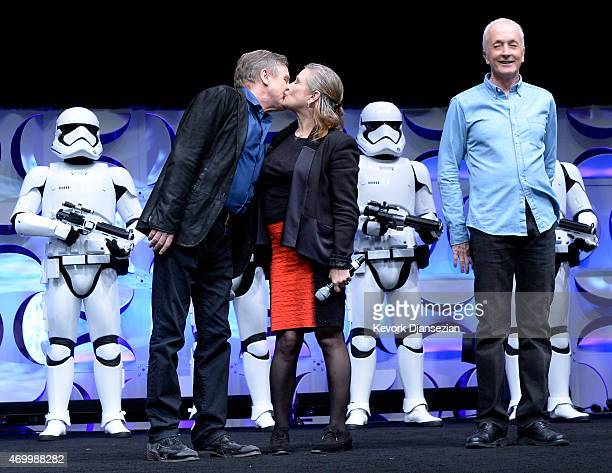 """Cast members of the original """"Star Wars"""" film Mark Hamill and Carrie Fisher kiss as Anthony Daniels looks on during the kick-off event of Disney's..."""