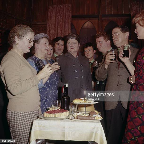 Cast members of the television soap opera Coronation Street pictured together holding drinks around a table of food during a scene on set in...