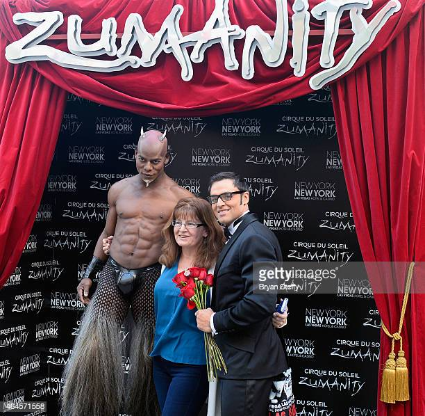 Cast members pose for a photo with a fan during a special outdoor performance of Zumanity The Sensual Side of Cirque du Soleil at the New YorkNew...