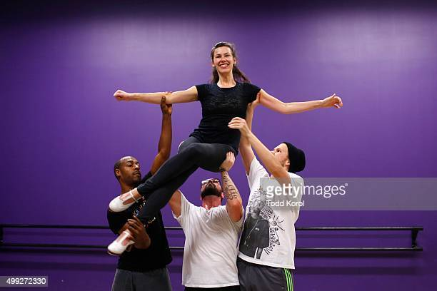 Cast members Travis Knights Ryan Foley and Danny Nielsen lift Allison Foley while rehearsing for the Big Band Tap Revue in Toronto, Ontario.