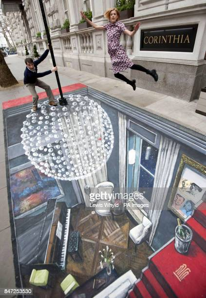 Cast of The Leisure Society Ed Stoppard and Agyness Deyn pose outside the Corinthia Hotel London on a piece of 3D Street Art created by Joe Hill who...