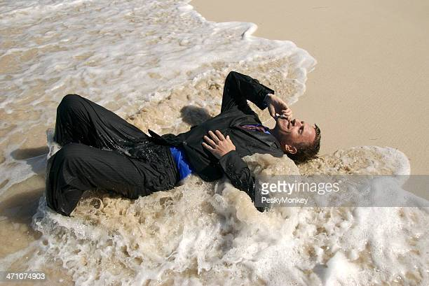 Castaway Businessman Lies in the Waves Talking on Mobile