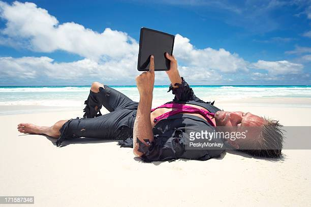 Castaway Businessman Relaxes with Digital Tablet on Beach