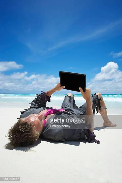 Castaway Businessman Uses Tablet Computer on Beach
