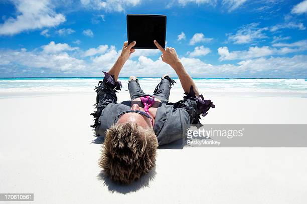 Castaway Businessman Using Tablet Computer Outdoors on White Beach
