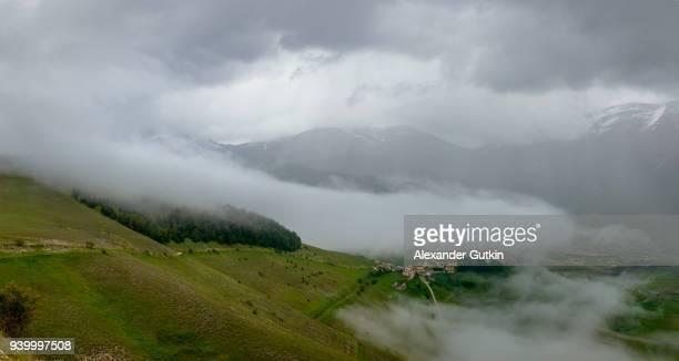 castelluccio di norcia morning fog. umbria. italy. - castelluccio stock photos and pictures