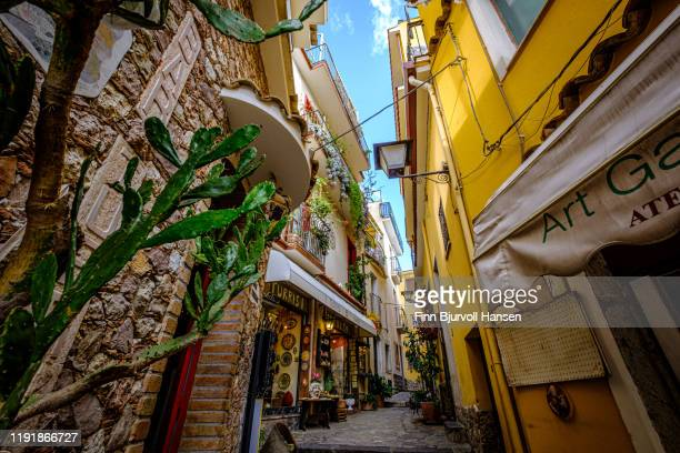 castelmola,taormina,sicily,italy - november 8, 2019 - narrow street with souvernirshop and art gallery, cactus in forground - finn bjurvoll - fotografias e filmes do acervo