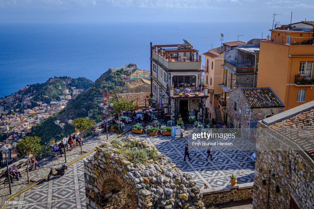Castelmola,Taormina,Sicily,Italy - November 8, 2019 - Piazza S. Antonio, image taken from the steps of Castello di Mola, mediteranian in the background : Stock Photo