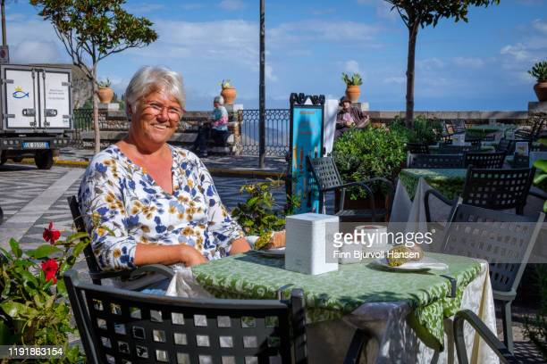 castelmola,taormina,sicily,italy - november 8, 2019 - woman enjoying a cappuccino and a canolo outdoor - finn bjurvoll stock photos and pictures