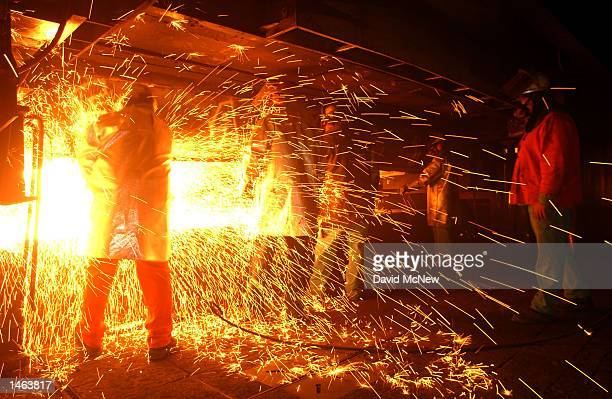Casters are showered with sparks or skeeters as molten steel is shaped into bars called billets at the TAMCO steel mini mill on October 4 2002 in...