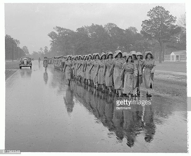Casting a reflection on the wet road are groups of women in the military or specifically the Marines as they march to chow and classes at Camp...