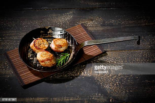 Cast-iron frying pan with medaillons of pork wrapped in bacon